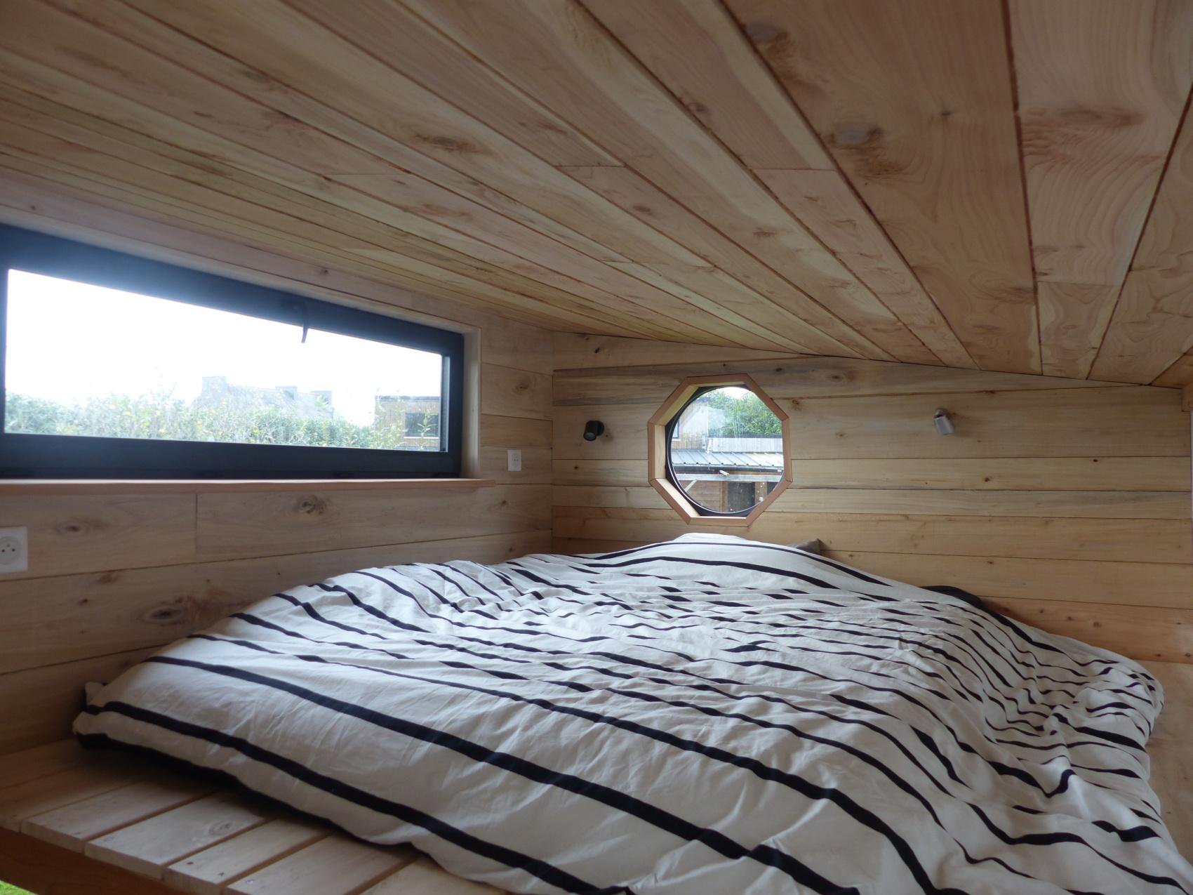 couchage double en mezzanine de la tiny house autonome avec fenêtre à battant en aluminium et double vitrage et hublot double vitrage alu