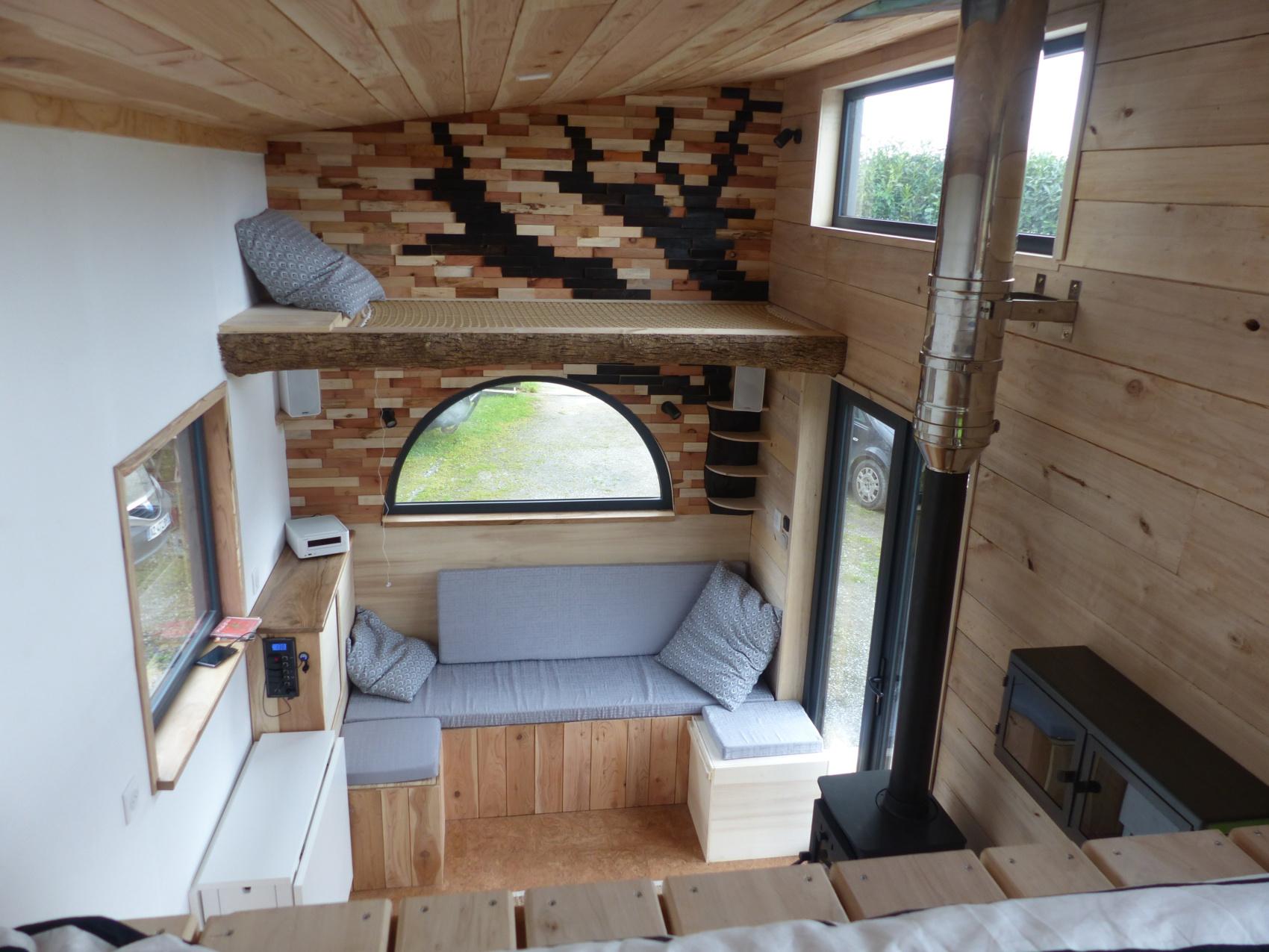tiny house autonome avec imposte, ouverture en aluminium double vitrage en demi-lune, couchage d'appoint en hauteur, couchage double