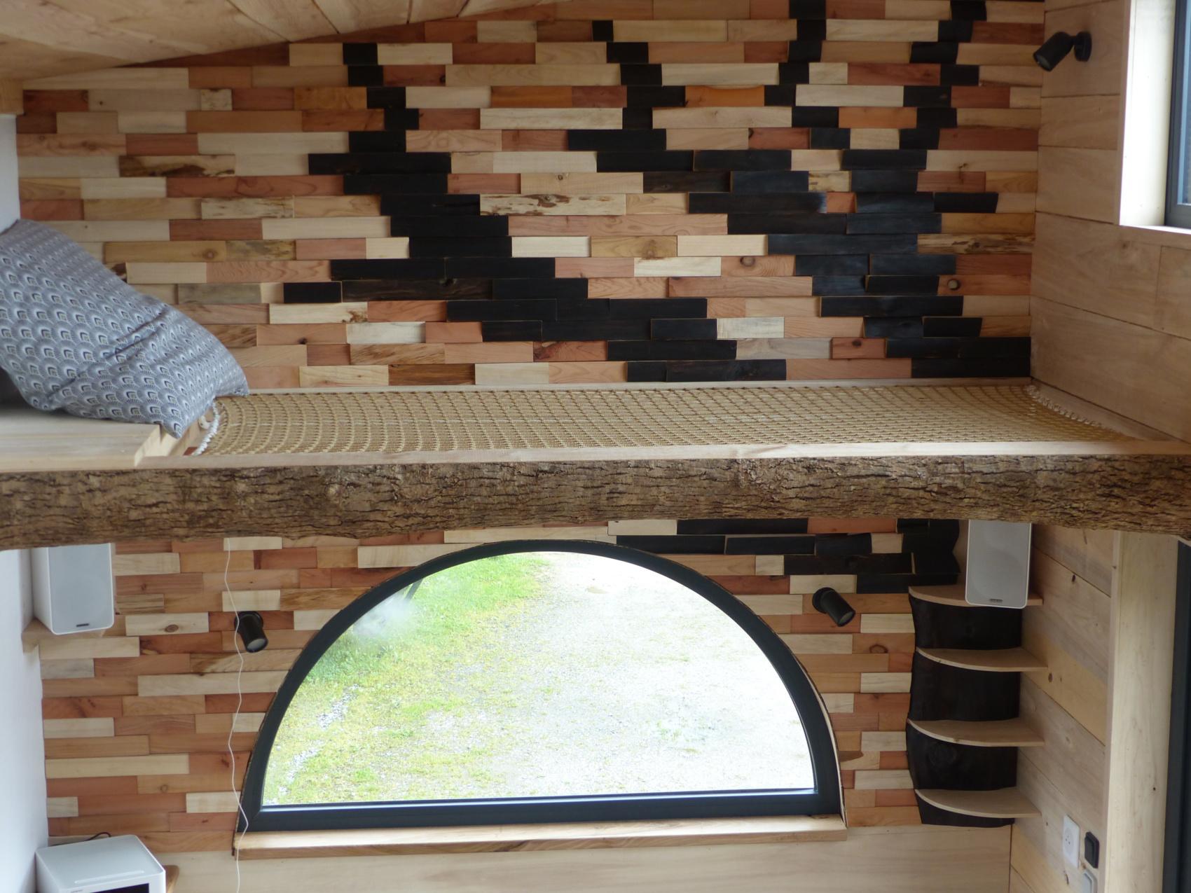 pignon est de la tiny house autonome avec ouverture en aluminium double vitrage en demi-lune et couchage d'appoint